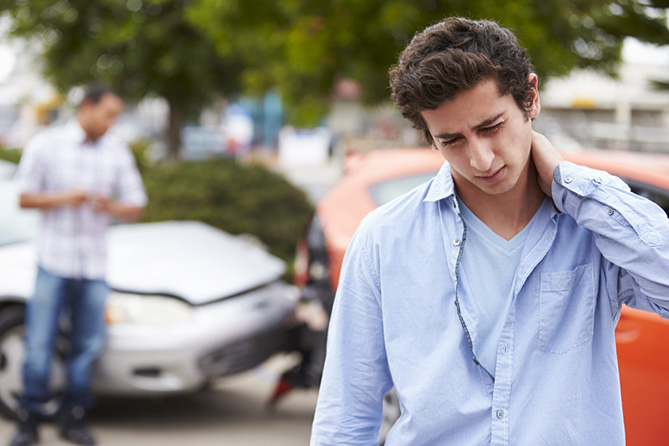 Young male holding his neck in pain with his crashed car behind him.