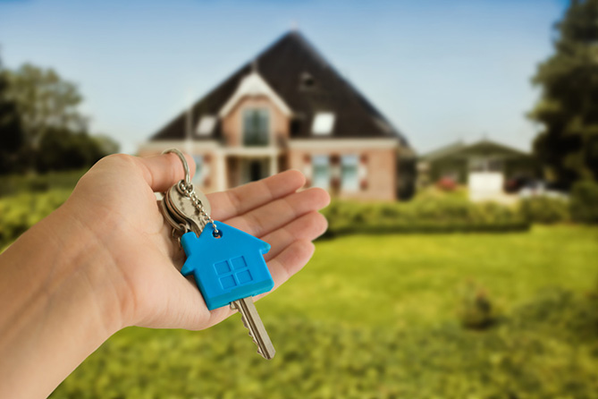 Buy or sell your home - Someone holding a set of house keys with a new house in the background.