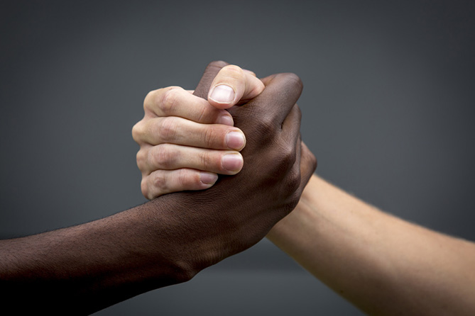Two people from different races shaking hands.