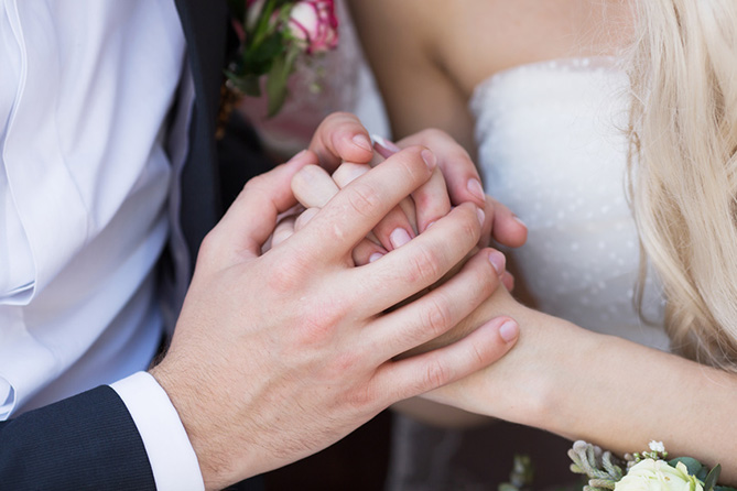 Close up of newly-weds holding hands on their wedding day.